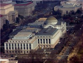 An aerial view of a white stone neoclassical building. There is a large brown dome towards the front and center of the building where the entrance is.