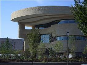A large curving beige stone building with bands of windows delineating each floor. The curving roof line extends out beyond the building and steps back twice to reach the rest of the structure.