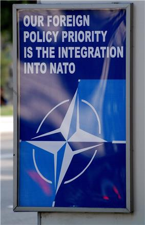 A blue poster at a bus stop with the NATO logo and the words