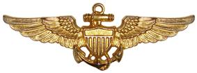 A golden badge depicting a shield superimposed over an anchor and a pair of wings