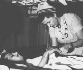 Navy Nurse caring for the wounded aboard USS Haven during Korean War.