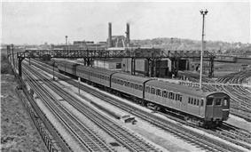 A black and white image of an electric multiple unit on the furthest of four tracks.