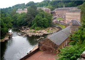 Several red brick factory buildings on the banks of a river which makes a hairpin turn. The buildings are surrounded by mountains and forest.