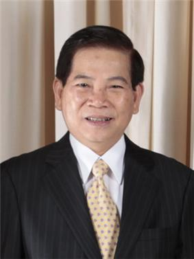 a smiling man with black hair, dressed in a suit with a white shirt and yellow tie