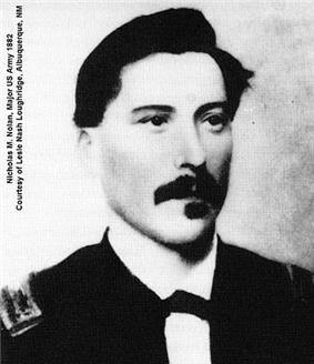 Black and white picture of a white male with a full dark mustache and squared goatee facing the camera and looking slightly to the right. He has dark swarthy hair neatly combed over a broad forehead. His dress uniform has a white collar with the front ends turned down with a small bow tie.