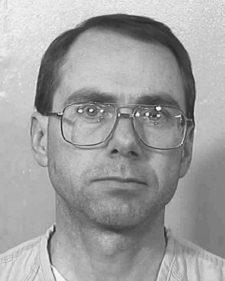 black and white photograph of a white male in his mid 30s, with thinning black hair, thick eyebrows, wearing very large, thick glasses with square frames