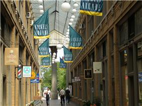 Atrium of a shopping arcade, with green and yellow banners hanging overhead with the words
