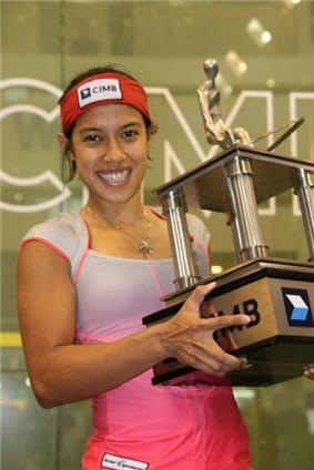 A young woman in a white-and-pink shirt and a red headband hoists a large squarish trophy, which has four pillars and a figurine at top.