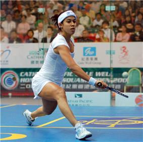 A young female squash player in white, stretching out to get her racket under a low ball, on a blue court with yellow markings, in front of a large, out-of-focus crowd behind glass.