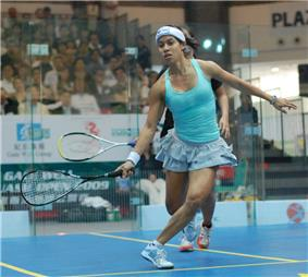 An indoor squash-court; a female player in light blue sportswear, a short pleated skirt, balancing for a shot, facing the camera and mostly obscuring her partner who is behind her. Both their rackets are at knee level on their left. A crowd is in the background, behind glass.