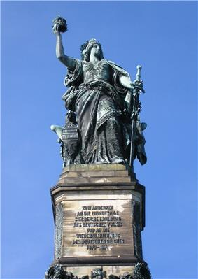 allegorical figure of Germania (woman with flowing robes, sword, flowing hair) standing, holding crown in right hand, sword partially sheathed