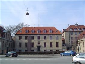 A block shaped beige building with a sloped, red tiled roof