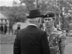 A black-and-white photograph of a soldier and a gentleman in a dark suit and hat shaking hands. The man in the suit is facing away from the camera. The soldier wears a dark-coloured beret with insignia on it and a camouflage shirt on which the sleeves are rolled up. A cross-shaped medal is prominent on his chest pocket. In the background, out of focus, four dark figures can be seen.