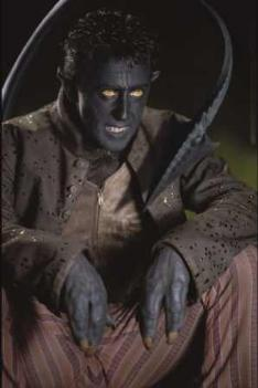 Close up of a sitting man with hands like claws, a long, pointed tail, pointed ears, and an intimidating, ghoulish expression on his face.