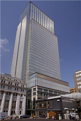 Ground-level view of a rectangular, glass high-rise; adjoining the high-rise is a stone building featuring columns