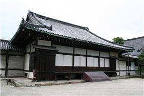 Wooden building with a hip-and-gable roof and white walls.