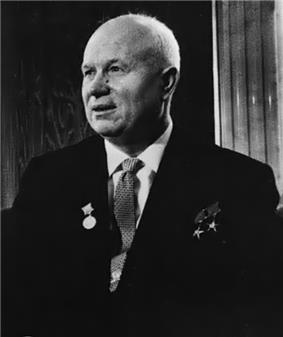 An elderly man in a suit, with three medals pinned on it