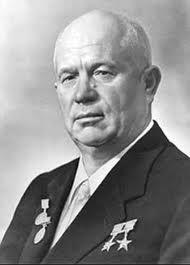 A portrait shot of an older, bald man with three medals on his chest. He is wearing a blazer over a collared shirt and tie.