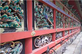 Wooden wall with red beams and colored carvings of plants, peacocks and other birds.