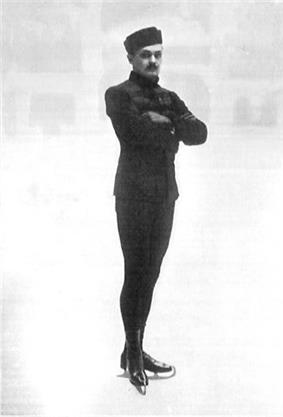 A male figure skater poses with crossed arms for a shot at an indoor ice rink; the background is very blurred.