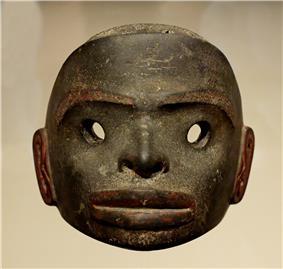 A dark stone mask, free standing