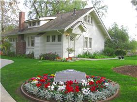 Photograph of the Richard M. Nixon Birthplace, a single-level, tree-shaded, white, wood-frame house.