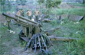 A damaged artillery piece sits in the foreground while a number of rifles resting against it. In the background a number of caucasian soldiers stand in the background next to a hootchie.