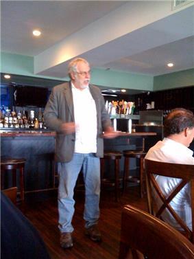 Nolan Bushnell speaking in a coffee shop