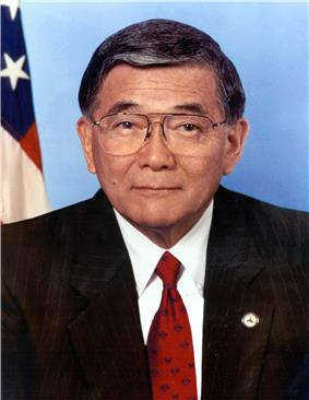 Older Japanese American man with glasses wearing a suit with a red tie with the US flag behind him