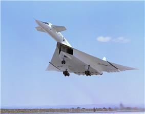 White delta-wing aircraft taking off with landing gears retracting. At the front of aircraft are canards.
