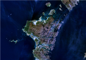 An indistinct image from space of brown and green islands in dark blue water.