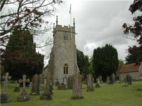 Stone church tower with flag pole. In the foreground are gravestones on grass.