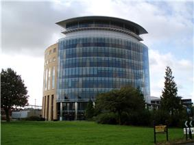 A semi-circular cylinder shaped tower building that is ten storeys tall, faced in glass and sandstone