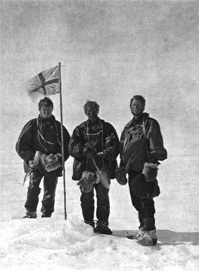 Three men stand around a flag planted in the snow.