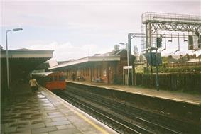People walking on a wet railway platform with grey lampposts on either side of a railway track on which a red train is running all under a blue sky