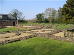Low stone walls form squares and other shapes and are surrounded by grassed areas. In the background to the left is the rear of the undercroft, and trees are in the background.
