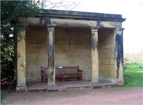 A open stone structure with four columns supporting a lintel. Inside the loggia is a wooden seat.