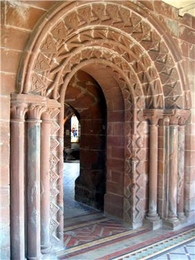 A highly decorated arched Norman doorway with a further, lower, arch beyond leading to a room with a window containing stained glass.