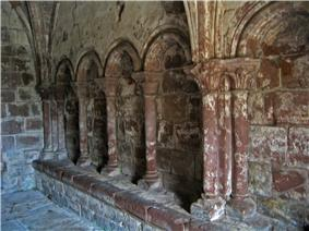A blind arcade seen from an angle showing four round-headed arches supported on columns with carved capitals; a bench runs along the base