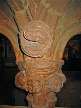 The top of a column and base of two arches. In the spandrel is a carving of an otter-like creature; the capital is decorated with a carved head and foliage