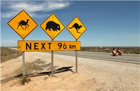 Warning signs stand out as the only feature along side a road through a flat, treeless, landscape