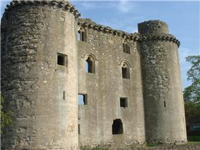 Ruined stone castle with round towers at each corner.