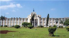 A wide four storied building with landscaped lawn and garden in the foreground