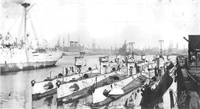 Nine submarines sit moored next to each other against a dock, with ships in the background