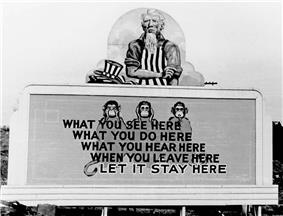 Uncle Sam has removed his hat and is rolling up his sleeves. On the wall in front of him are three monkeys and the slogan: What you see here / What you do here / What you hear here / When you leave here / Let it stay here.