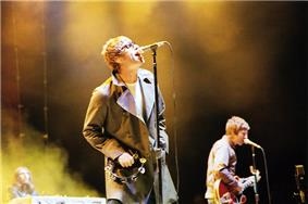Two-thirds body shot of a singer wearing a coat with wide lapels; a guitar player is in the background. Both have short, blond hair.