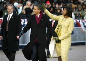 Barack and Michelle Obama acknowledge the crowd while the Secret Service and onlookers watch.
