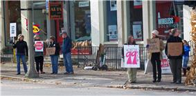 A group of seven people holding hand-lettered cardboard signs along a city street. The largest says