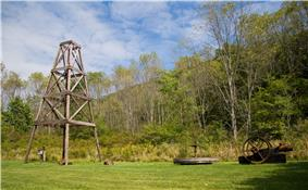 A wooden derrick at left on grass, with trees and a mountain ridge in the background