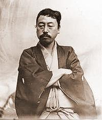 Portrait of an Asian man with moustache dressed in traditional Japanese cloths. He is looking down with his arms crossed.